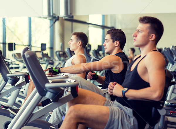 men working out on exercise bike in gym Stock photo © dolgachov