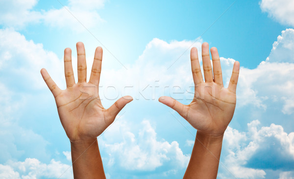 two african hands making high five over blue sky Stock photo © dolgachov
