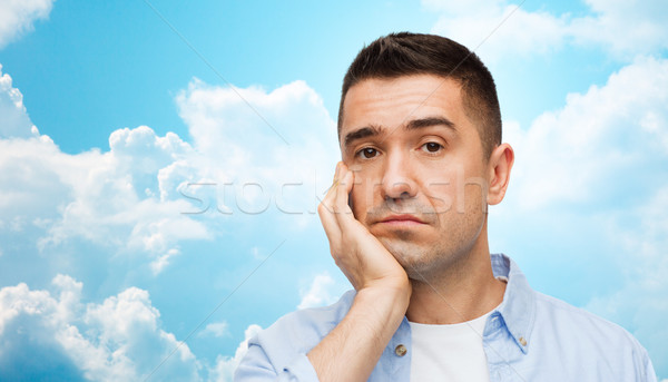 bored man face over blue sky and clouds background Stock photo © dolgachov