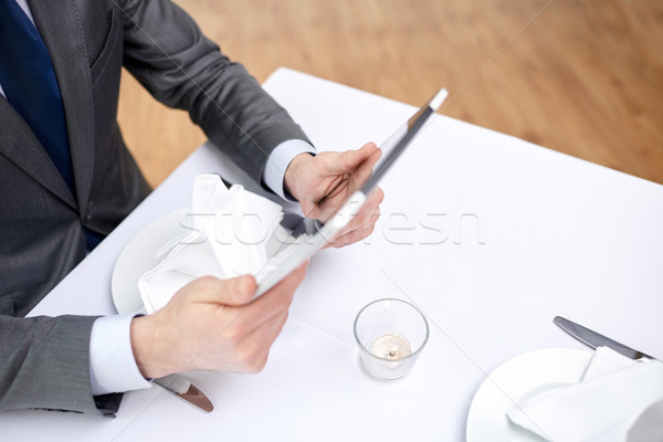 close up of man with tablet pc at restaurant Stock photo © dolgachov