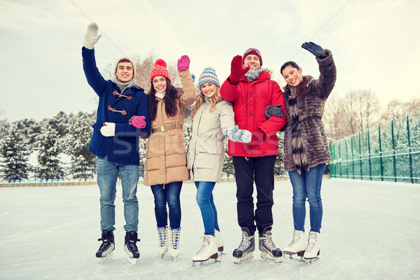 Stock photo: happy friends ice skating on rink outdoors