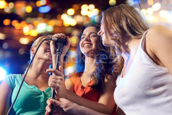 happy young women singing karaoke in night club Stock photo © dolgachov