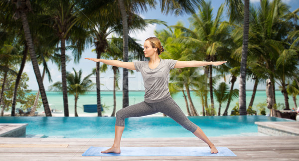 woman making yoga warrior pose over hotel resort Stock photo © dolgachov
