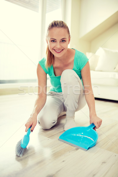 happy woman with brush and dustpan sweeping floor Stock photo © dolgachov