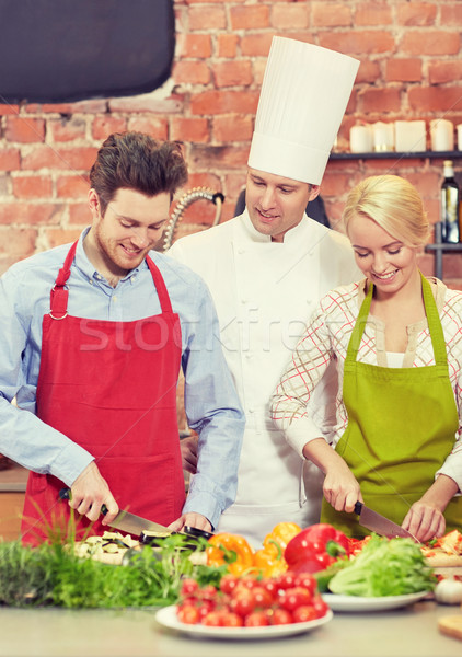 happy couple and male chef cook cooking in kitchen Stock photo © dolgachov