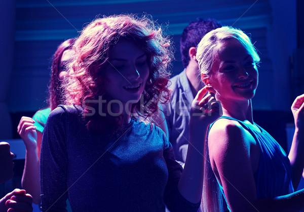 group of happy friends dancing in night club Stock photo © dolgachov