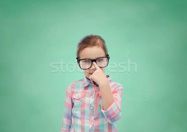 happy little girl in eyeglasses over school board Stock photo © dolgachov