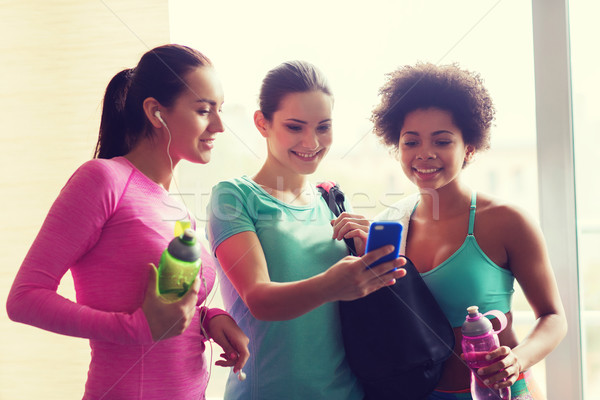 happy women with bottles and smartphone in gym Stock photo © dolgachov