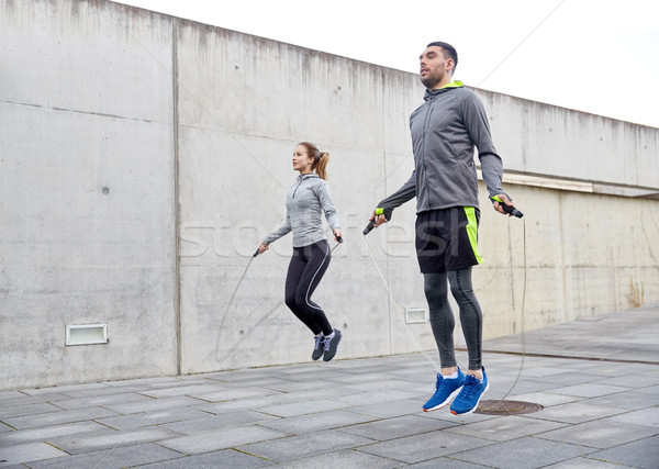 man and woman exercising with jump-rope outdoors Stock photo © dolgachov