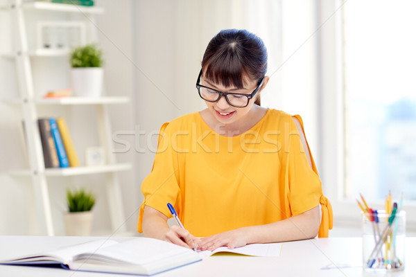 Stock photo: happy asian young woman student learning at home