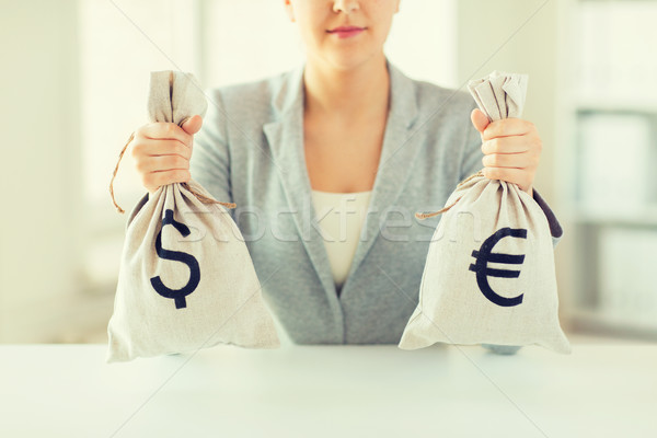 Stock photo: close up of woman hands holding money bags