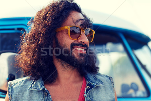 smiling young hippie man over minivan car Stock photo © dolgachov