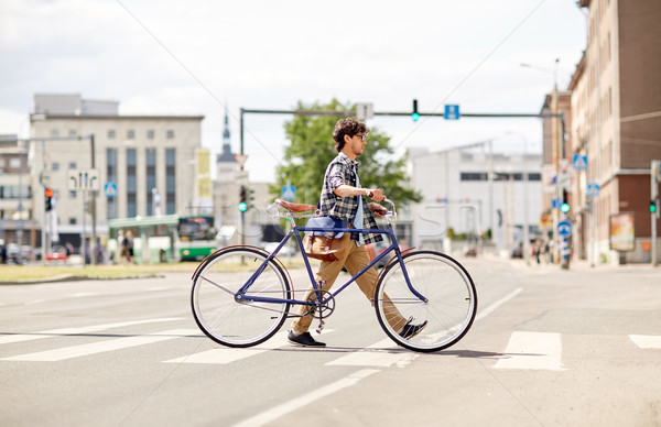 young man with fixed gear bicycle on crosswalk Stock photo © dolgachov