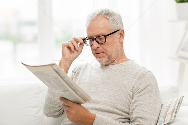 senior man in glasses reading newspaper at home Stock photo © dolgachov