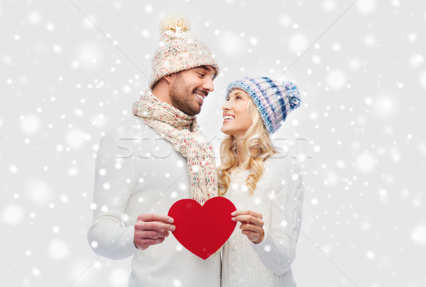 smiling couple in winter clothes with red heart Stock photo © dolgachov