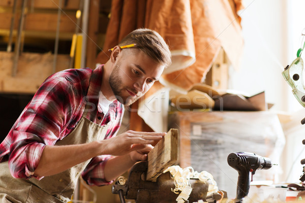 carpenter working with wood plank at workshop Stock photo © dolgachov