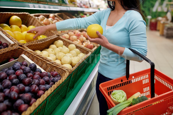 woman with basket buying pomelo at grocery store Stock photo © dolgachov
