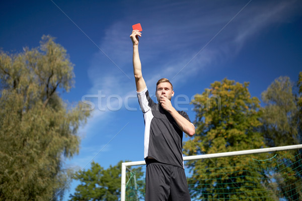 referee on football field showing yellow card Stock photo © dolgachov