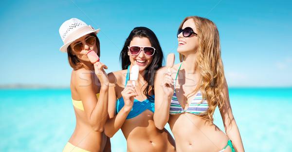 group of smiling women eating ice cream on beach Stock photo © dolgachov