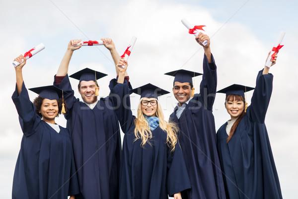 happy students in mortar boards waving diplomas Stock photo © dolgachov