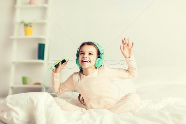 Dziewczyna posiedzenia bed smartphone słuchawki ludzi Zdjęcia stock © dolgachov