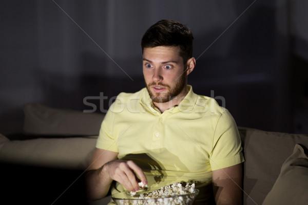 Férfi néz tv eszik pattogatott kukorica éjszaka Stock fotó © dolgachov