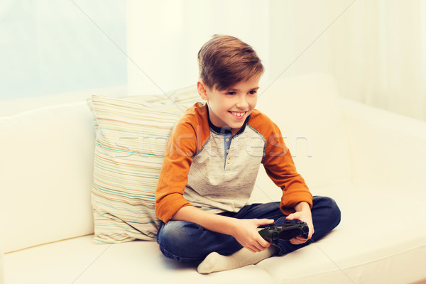 happy boy with joystick playing video game at home Stock photo © dolgachov