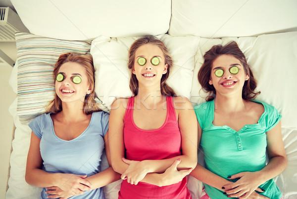 Szczęśliwy młodych kobiet ogórek maska bed ludzi Zdjęcia stock © dolgachov