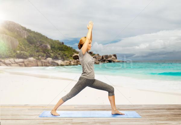Feliz mujer yoga guerrero plantean playa Foto stock © dolgachov