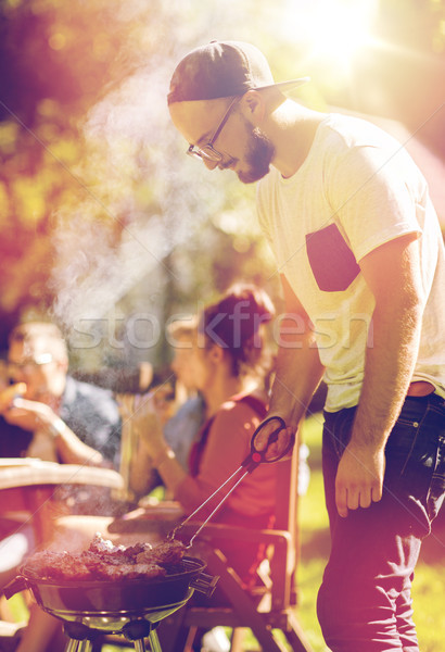 man cooking meat on barbecue grill at summer party Stock photo © dolgachov
