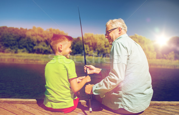 grandfather and grandson fishing on river berth Stock photo © dolgachov