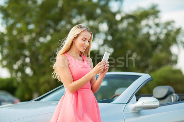 young woman with smartphone at convertible car Stock photo © dolgachov