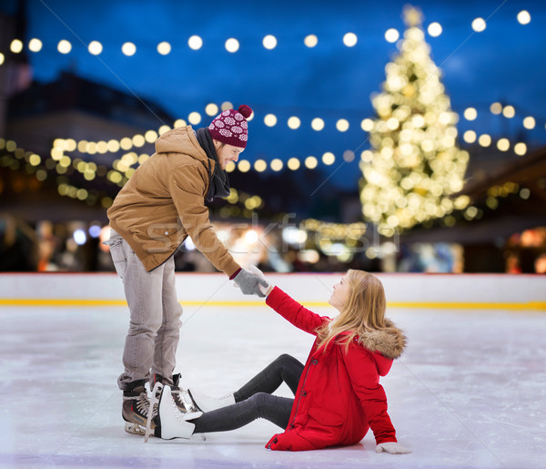 man helping woman on christmas skating rink Stock photo © dolgachov