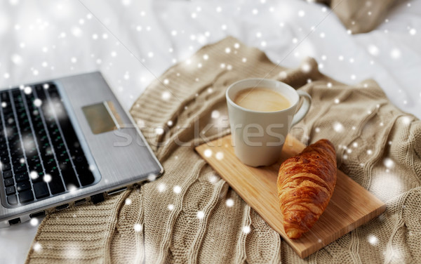 laptop, coffee and croissant on bed at cozy home Stock photo © dolgachov