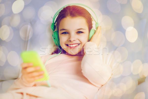 少女 ヘッドホン 音楽を聴く ベッド 人 子供 ストックフォト © dolgachov