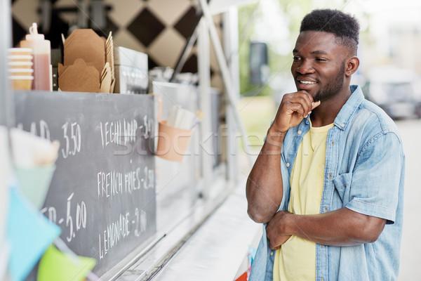 male customer looking at billboard at food truck Stock photo © dolgachov