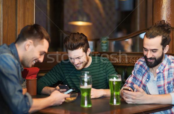 Amigos smartphones verde cerveja pub lazer Foto stock © dolgachov