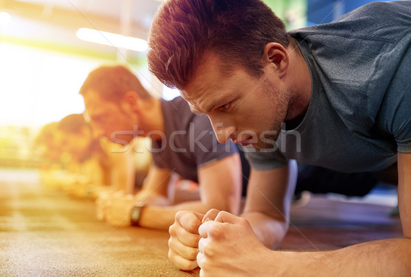 man doing plank exercise at group training in gym Stock photo © dolgachov