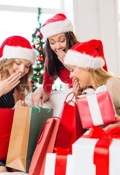 women in santa helper hats with shopping bags Stock photo © dolgachov