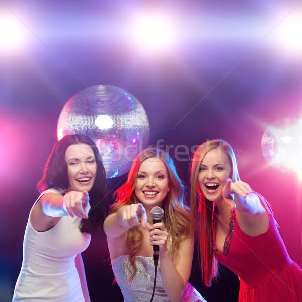 Drie glimlachend vrouwen dansen zingen karaoke Stockfoto © dolgachov