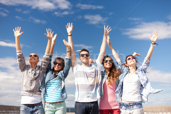 group of smiling teenagers holding hands up Stock photo © dolgachov