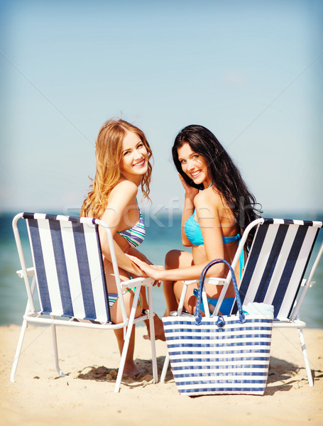 girls sunbathing on the beach chairs Stock photo © dolgachov