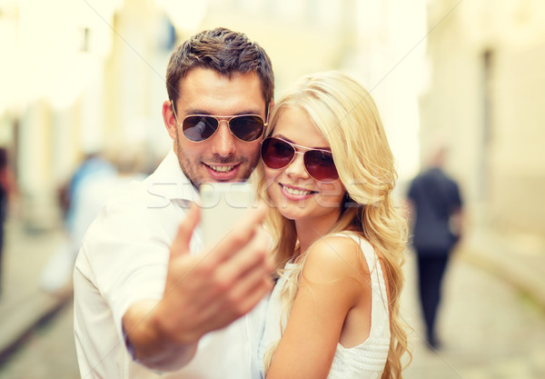 smiling couple with smartphone in the city Stock photo © dolgachov