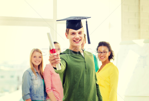smiling male student with diploma and corner-cap Stock photo © dolgachov