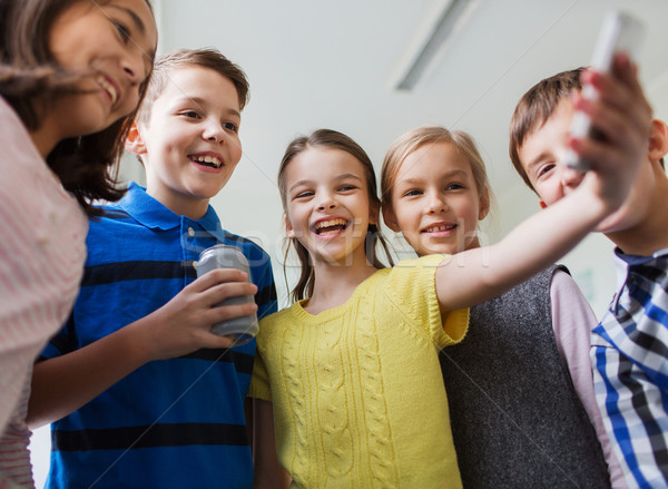 group of school kids with smartphone and soda can Stock photo © dolgachov