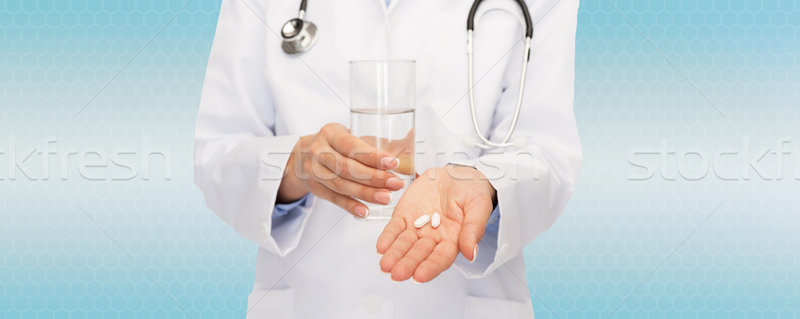 close up of doctor offering pills and water Stock photo © dolgachov
