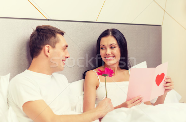 smiling couple in bed with postcard and flower Stock photo © dolgachov