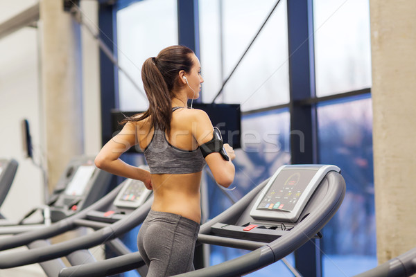 woman with earphones exercising on treadmill Stock photo © dolgachov