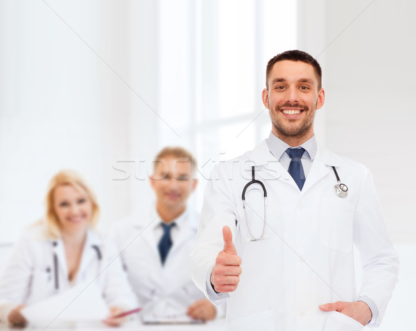 smiling doctor with stethoscope showing thumbs up Stock photo © dolgachov