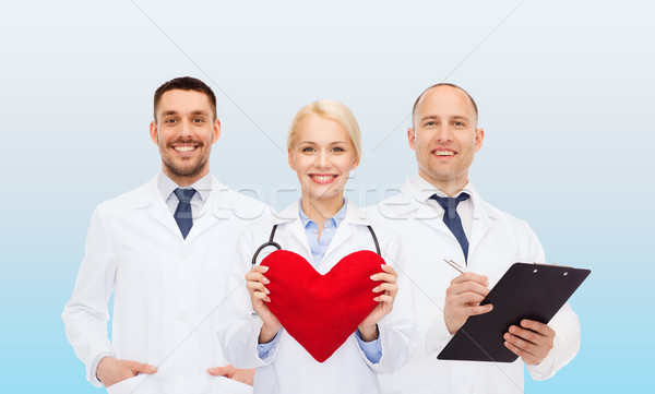 group of smiling doctors with heart and clipboard Stock photo © dolgachov